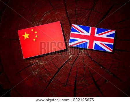Chinese Flag With British Flag On A Tree Stump Isolated