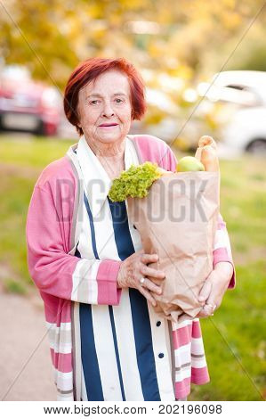 Smiling senior woman 70-80 year old holding paper bag with products outdoors. Looking at camera.