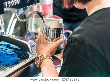 Asian Barista Steaming Fresh Milk In Stainless Pitcher With Vent Pipe