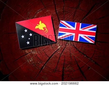 Papua New Guinea Flag With British Flag On A Tree Stump Isolated
