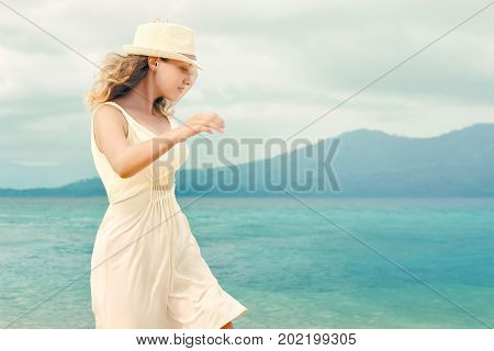 Pretty girl in a white dress walking on the beach before the rain Beach sunset nature evening. Love romance concept.