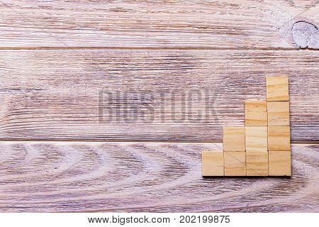 A wooden blocks cube over black wooden textured background with copy space for add word text title. Concept or conceptual Wood block stair or four steps. Cubic.