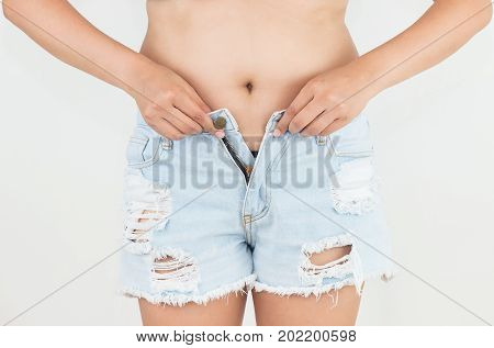 Woman trying to fasten jeans tight on belly fat Diet concept Weight lose concept.