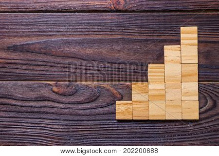 A wooden blocks cube over black wooden textured background with copy space for add word text title. Concept or conceptual Wood block stair or five steps. Cubic.