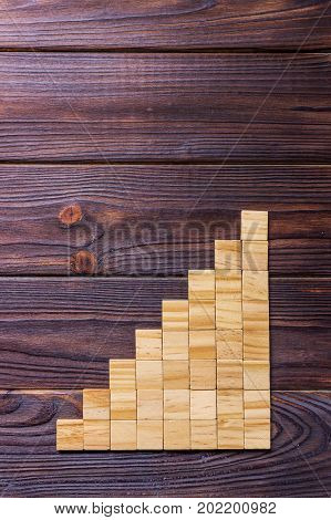 A wooden blocks cube over black wooden textured background with copy space for add word text title. Concept or conceptual Wood block stair or eight steps. Cubic.