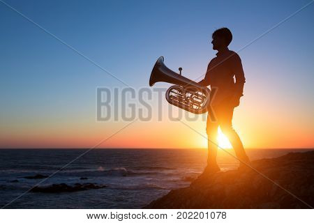 Silhouette of musician with Tuba on sea shore at sunset .