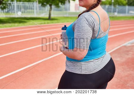 Midsection of plus-size sweaty girl with bottle of water during refreshment after workout on stadium