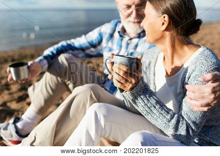 Amorous aged couple having tea while relaxing on the beach
