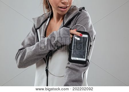 Cropped image of a female runner in warm clothes using blank screen mobile phone on armband over gray background