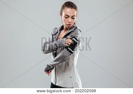 Side view of a sports woman using smartphone on armband over gray background