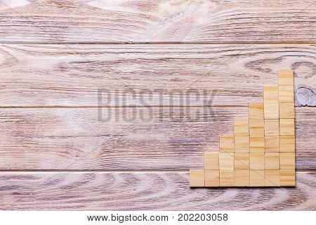 A wooden blocks cube over black wooden textured background with copy space for add word text title. Concept or conceptual Wood block stair or seven steps. Cubic.