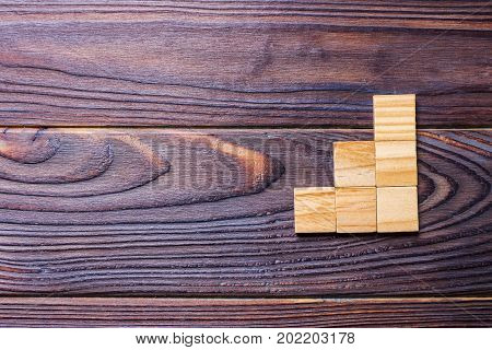 A wooden blocks cube over black wooden textured background with copy space for add word text title. Concept or conceptual Wood block stair or three steps. Cubic.