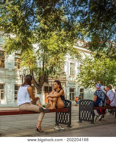 Orenburg, Russia - August 16, 2017: Two Attractive Girls Sitting On A Bench On The Street Lead A Liv