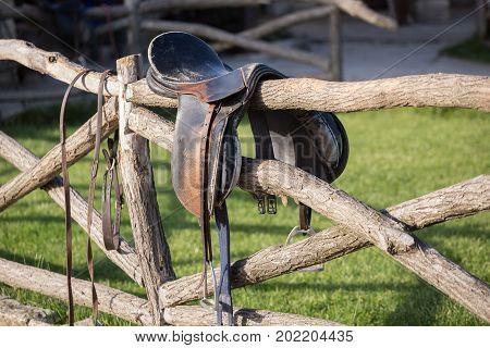 Vintage saddle on rural fence. Ranch scene