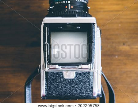Bird's eye view of a medium format camera viewfinder on rustic wooden countertop. Viewfinder is blank. Room for copy.
