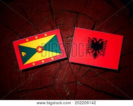 Grenada Flag With Albanian Flag On A Tree Stump Isolated