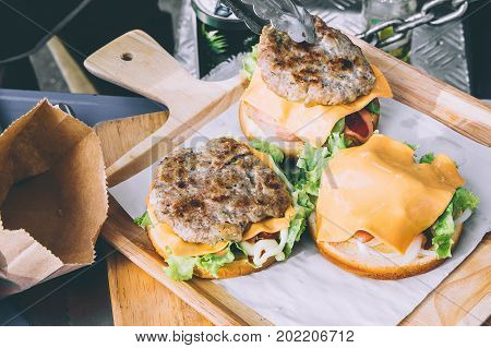 Delicious hamburgers delicious fast food vegetable salad ketchup And the cheese is stuffed in delicious bread on a wooden tray.