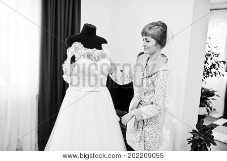 Portrait Of A Bride In Nightgown Posing With Her Wedding Dress In The Room. Black And White Photo.