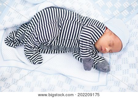 Sleeping newborn baby in striped romper mittens and beanie lies on side in blue coverlet.