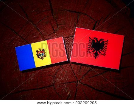 Moldovan Flag With Albanian Flag On A Tree Stump Isolated