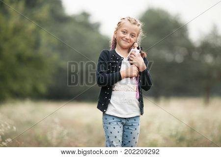 Child girl with pigtails smiles and plays with her doll on walk.