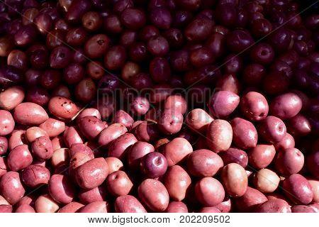 olives close up, many olives, red olives, olives lie half in sunshine half in shade