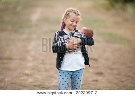Child girl with her newborn brother on walk. Girl holds newborn baby in her hands and looks him with love. Close up.
