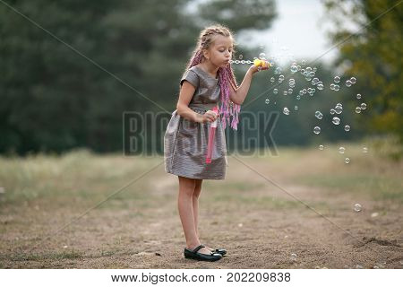 Happy child girl with pigtails blowing soap bubbles on walk in park.