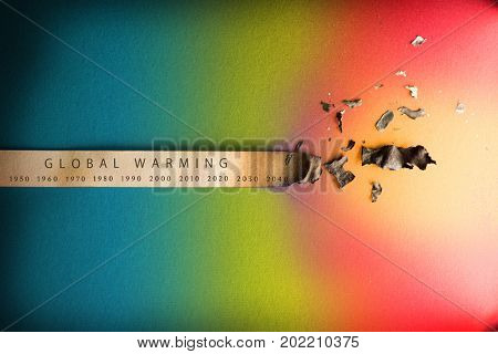 Global warming, Climate change, concept image. Rising temperature through the decades. Paper strip with timeline charred and burnt on the right end, placed on blue to red background.