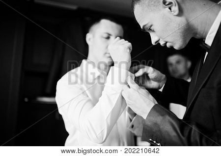 Groomsmen Helping Groom To Dress Up And Get Ready For His Wedding Ceremony. Black And White Photo.