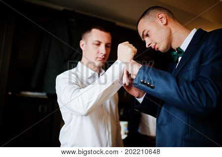 Groomsmen Helping Groom To Dress Up And Get Ready For His Wedding Ceremony.