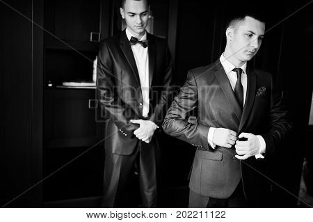 Groom Dressing Up In The Presence Of His Groomsmen In The Room. Black And White Photo.