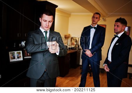 Groom Dressing Up In The Presence Of His Groomsmen In The Room.