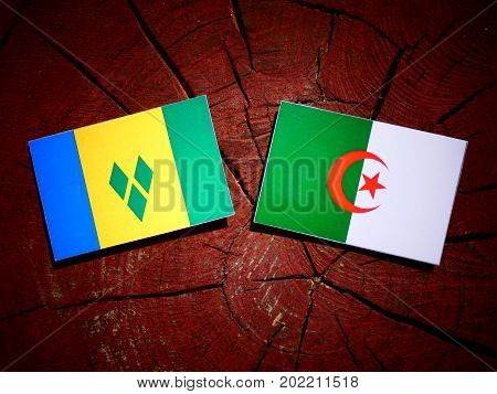 Saint Vincent And The Grenadines Flag With Algerian Flag On A Tree Stump Isolated