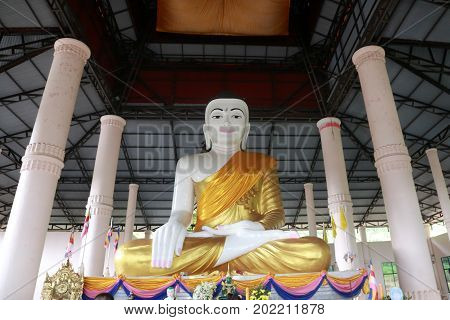 Antique white Buddha statue covered in golden yellow robes at temple in Myanmar.