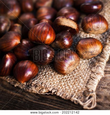 Ripe chestnuts on old wooden table and sack napkin close up with copy space. Roasted Chestnuts for Christmas