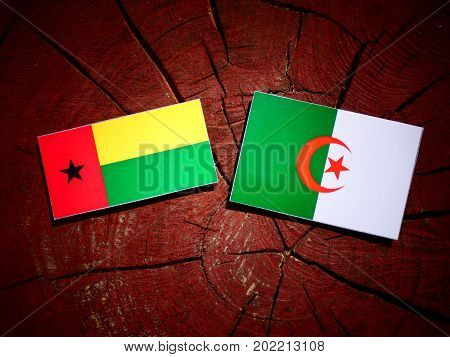 Guinea Bissau Flag With Algerian Flag On A Tree Stump Isolated