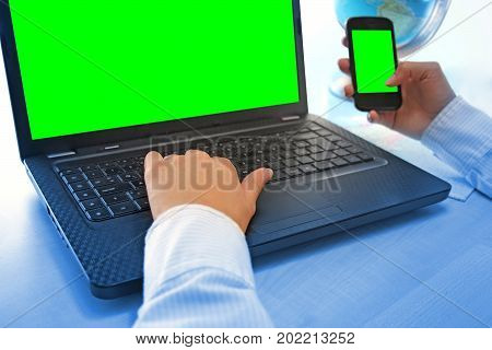 Women hands working on laptop and smart phone in office on green screen