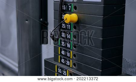Black iron heavy plates stacked of weight machine with kilogram and pound numbers in fitness gym
