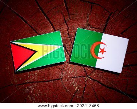 Guyana Flag With Algerian Flag On A Tree Stump Isolated