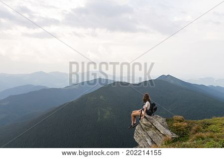 Young female hiker sits on rock in gorgeous mountain area and looks in endless horizon. Woman with tourist rucksack takes rest top of hill after reaching destination in carpathians