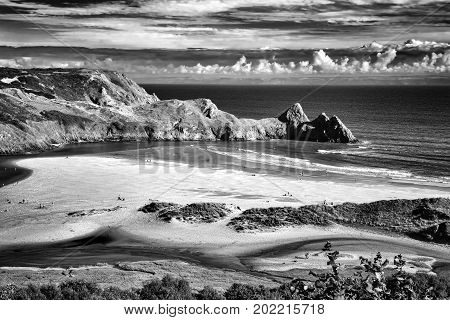 Black and white monochrome image of Three Cliffs Bay on the Gower Peninsular, West Glamorgan, Wales, UK, which is a popular Welsh coastline attraction of outstanding beauty