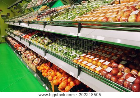 Shelves with fruits in food supermarket, visible labels removed, toned image