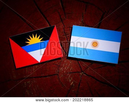 Antigua And Barbuda Flag With Argentinian Flag On A Tree Stump Isolated