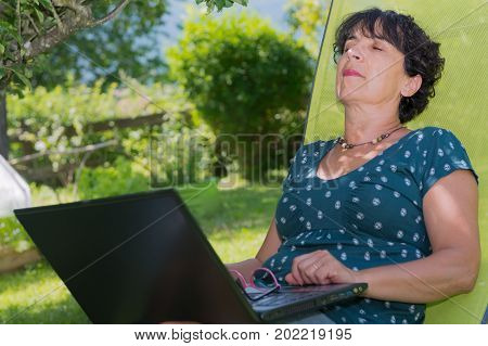 a mature woman relaxing resting on the deck chair in garden