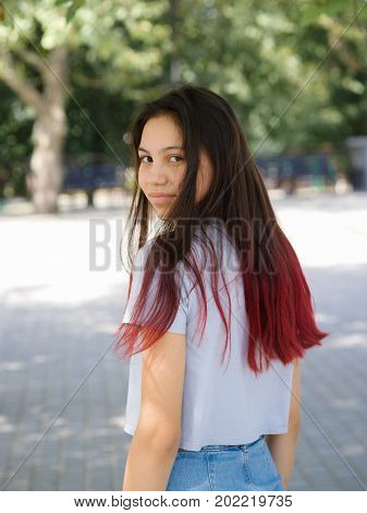 Close-up of a confident, trendy adolescence lady wearing a white T-shirt and denim skirt on a street blurred background. A beautiful and cute young girl with ombre hair posing in the outdoors.