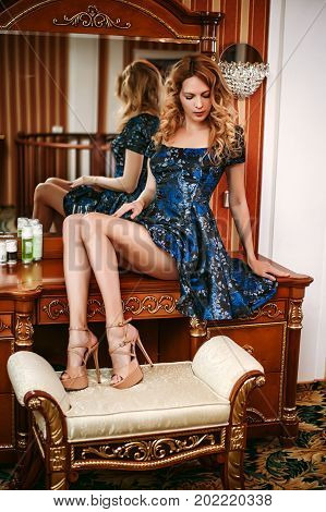 Beautiful girl wearing dark blue dress sitting on the table boudoir in the bedroom. Legs in sandals with high heels stand on a banquet
