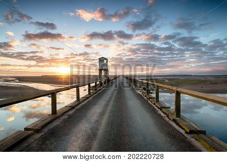 Sunrise over the causeway bridge that links the island of Lindsifarne with the mainland on the Northumbria coast looking out to the island and the hut used as a refuge for those stranded by the tide.
