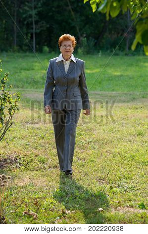 business woman of an age is walking in the park. Age eighty years. A woman in a business suit.