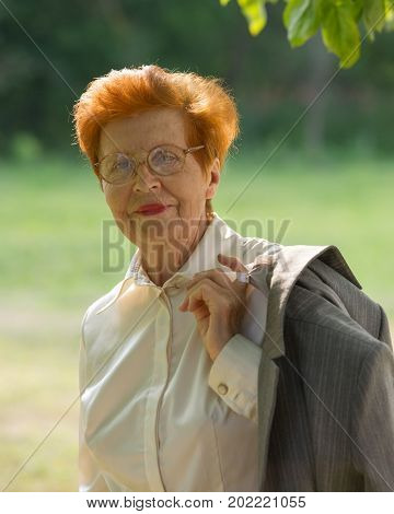Portrait of business woman aged against the background of the park. Age eighty years. A woman in a business suit.